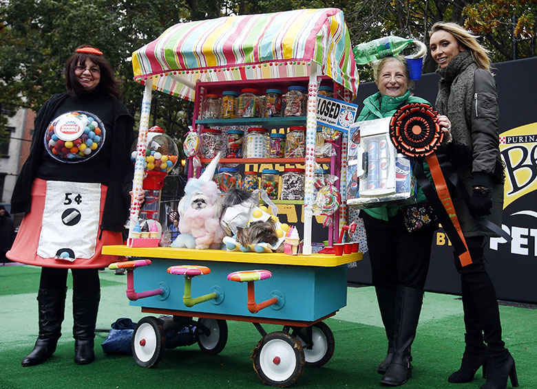 Host Giuliana Rancic poses with the best in show winners dressed as ìThe Sweet Shop at the Tompkins Square Halloween Dog Parade Image credit: Jason DeCrow/Invision for Purina Begginí and PetSmart/AP Images)